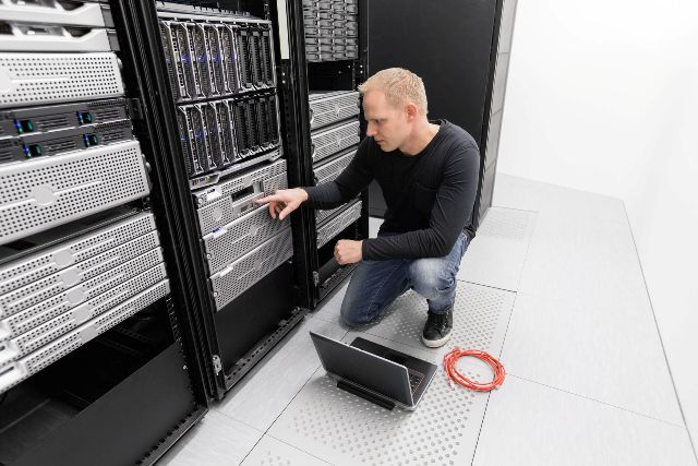 27864148 - it engineer or consultant working with backup server. shot in data center.